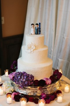 Custom wedding cake and topper with purple flowers